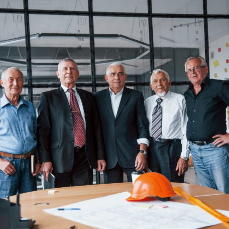 Aged team of elderly businessman architects stands in the office together.
